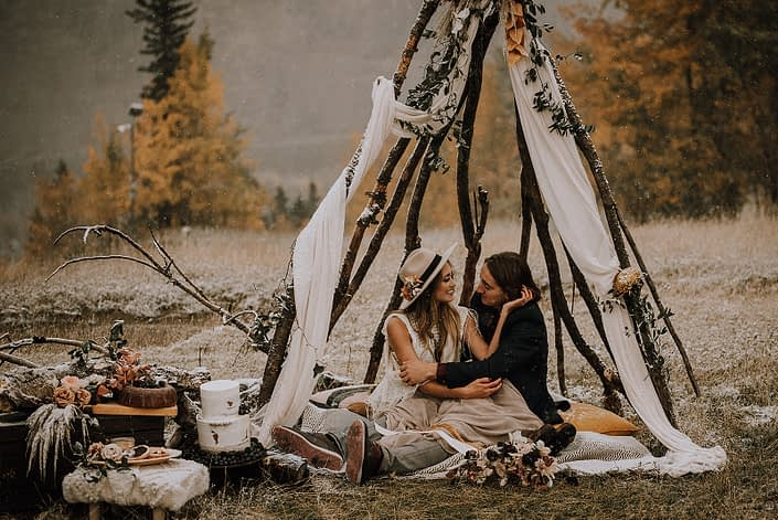 Couple sitting in a tee pee for down the aisle fall styled shoot