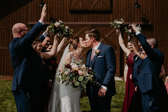 Bride and groom kissing surrounded by cheering bridal party; groom wearing boutonniere made of spray roses, sweet pea and astilbe; bride holding bridal bouquet featuring burgundy dahlias, burgundy cymbidium, astrantia, peach ranunculus, cappuccino roses, quicksand roses and a variety of eucalyptus greenery.