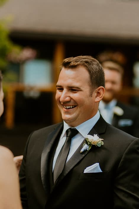 Groom wearing white boutonniere designed with spray roses and eucalyptus