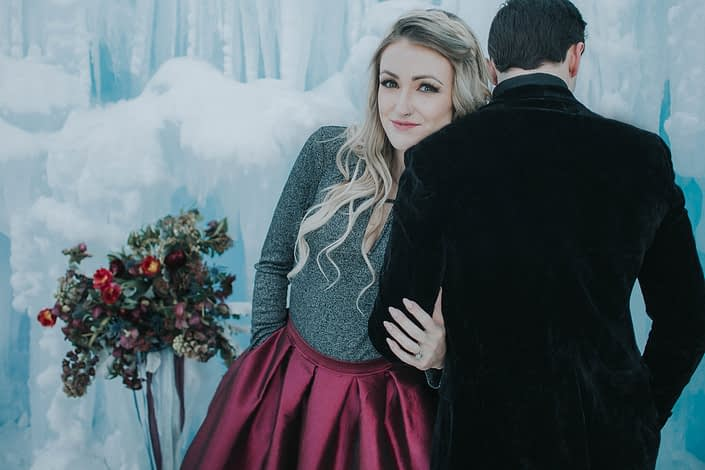 engagement photoshoot at the ice castles in edmonton with a burgundy taffetta dress and burgundy bridal bouquet