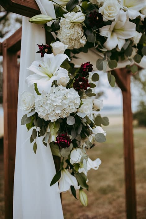 Archway arrangement designed with white lilies and hydrangea and roses and burgundy dahlia with white voile