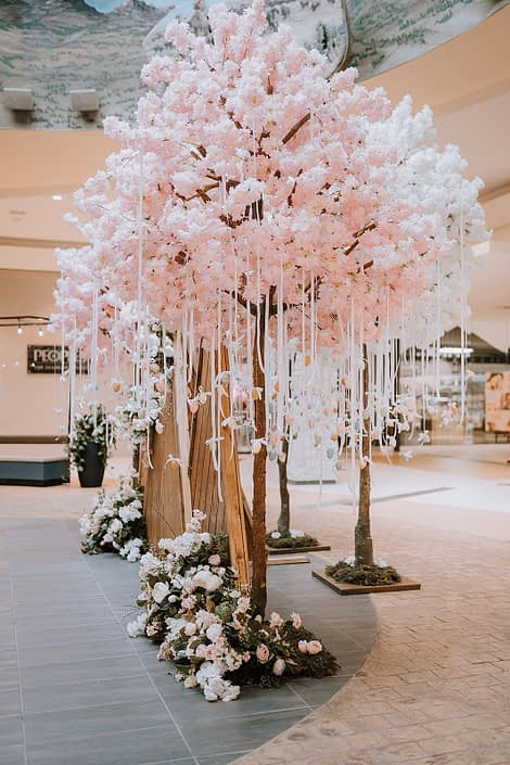 Artificial pink tree with Easter eggs hanging from it and artificial flowers at the base