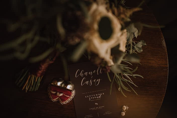 close up photo of brides rings and invitation with burgundy and ivory bridal bouquet