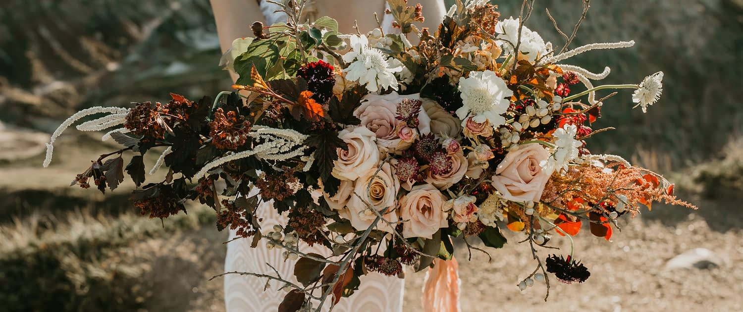 bride holding bridal bouquet designed with burgundy leaves, blush quicksand roses, white scabiosa and white amaranthus