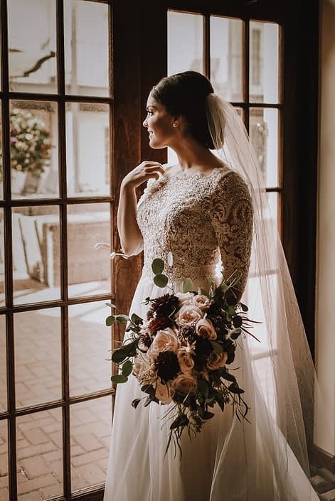 bride in long sleeved lace top wedding dress wth cathedral veil holding a bridal bouquet designed with burgundy dahlia, ivory garden roses and blush garden roses