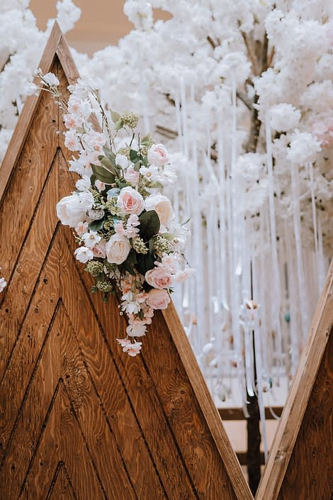 Wooden mountain backdrop decorated with an arrangement of white, peach and pink artificial flowers