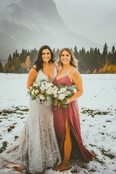 Blush and Mauve Canmore Wedding - Meagan and her maid of honour standing in a snow covered field in the Rocky Mountains. The bride is wearing a champagne and ivory lace bridal gown and carrying a stunning bouquet with greenery and blush, mauve and white flowers including roses, panda anemones and ranunculus. Her maid of honour is wearing a floor-length mauve dress and carrying a simpler blush, white and mauve bouquet.