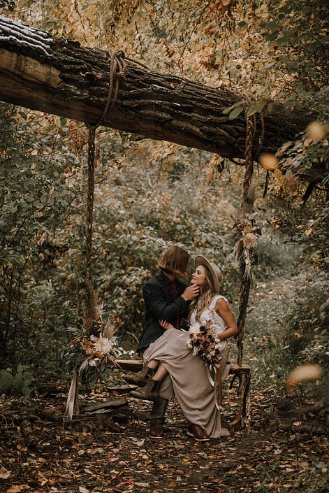 Down the aisle fall styled shoot - Couple in the woods on a swing with neutral fall flowers