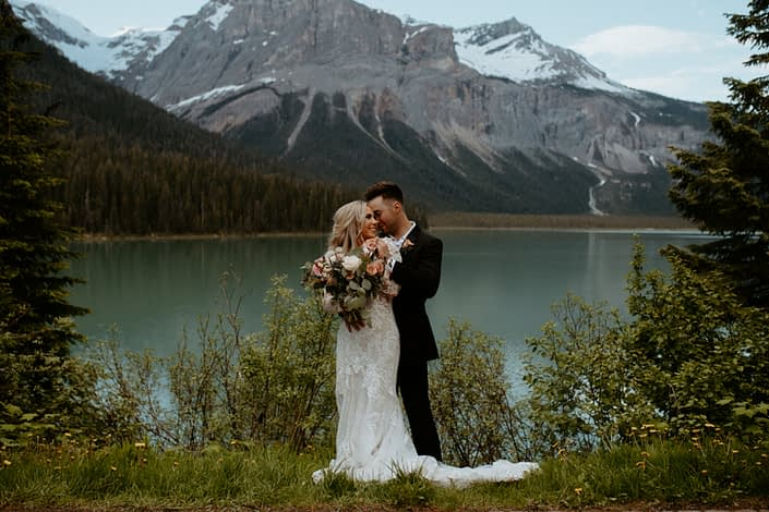 Bride and groom with bridal bouquet alongside Emerald Lake with a view of the Rocky Mountains