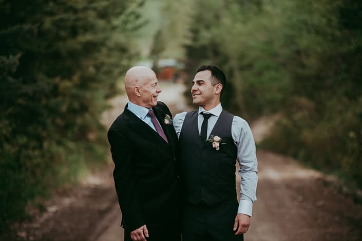 Groom and son wearing blush spray rose boutonnieres accented with burgundy ninebark leaves and juniper.