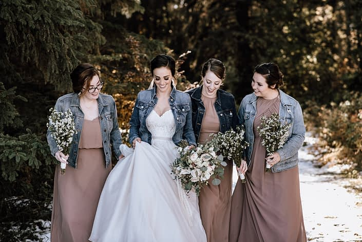 bride and bridesmaids in jean jackets and dusty rose dresses with white rose and waxflower bouquets