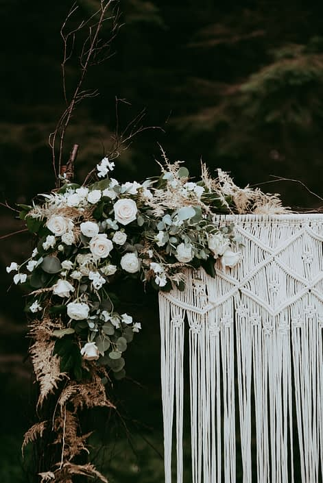 Natural white and green wedding woven twig archway decorated with macrame and a corner arrangement made of white astilbe, ranunculus, Tibet roses, spray roses, sweet peas, Italian ruscus, eucalyptus and gold plumosa