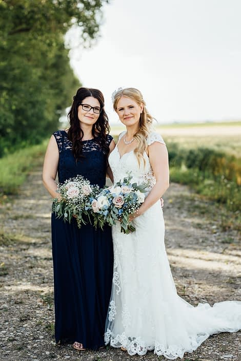 Bride, Kelsie, and bridesmaid with bouquets made of quicksand roses, white o'hara garden roses, succulents, babies breath, blue delphiniums, and eucalyptus greenery.