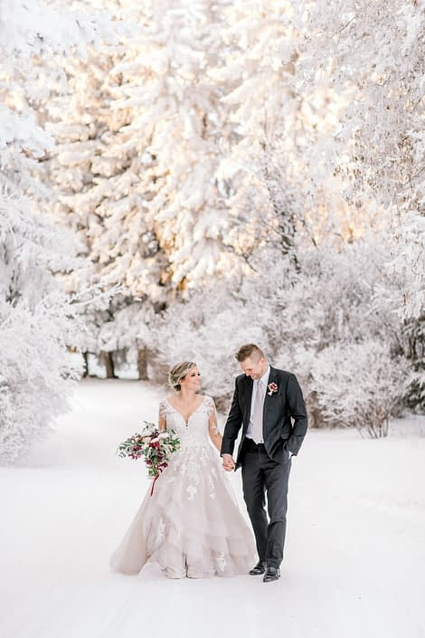 Bride and groom walking in a snowy winter wonderland with blush and burgundy bridal bouquet; blush and burgundy winter photoshoot