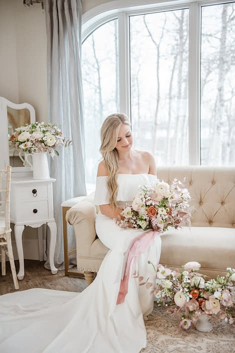 Bride holding white, pink and rose gold bridal bouquet surrounded by floral arrangements in a bridal suite
