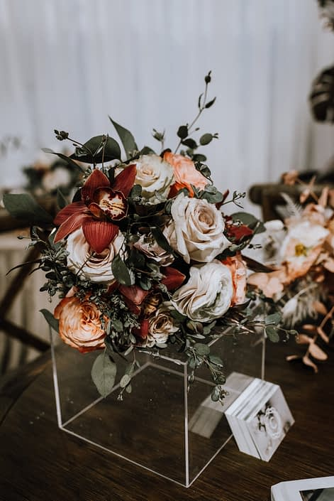 An arrangement at the With This Ring 2020 featuring red orchids, orange roses, ivory roses and ranunculus with eucalyptus greenery.