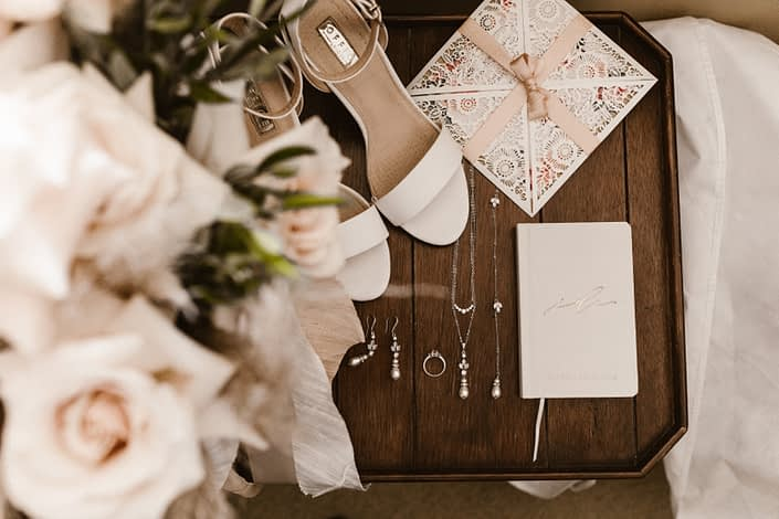 Sandra's blush and ivory bridal flat lay including shoes, jewelry, ring, invite, flowers and vows.