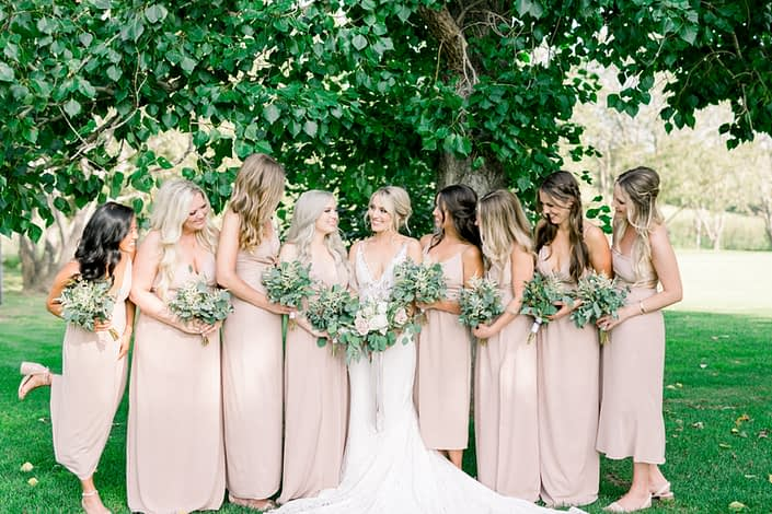 Kayla wearing a white lace dress and holding a white and blush bouquet surrounded by her bridesmaids wearing blush floor-length dresses and holding bouquets made of white astilbe, olive branches and eucalyptus greenery.