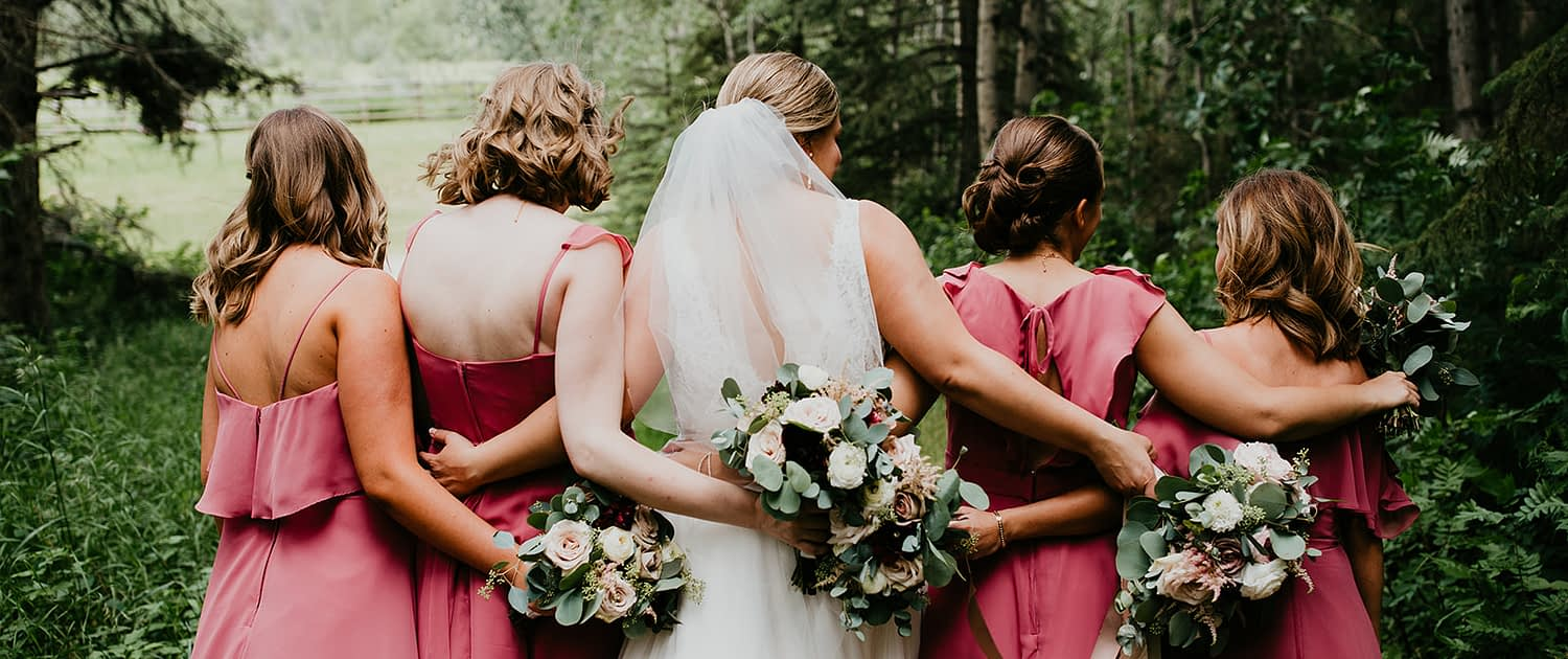 Briana and Mark's Glam Jewel Tone Wedding - Bride and bridesmaids with their backs to the camera holding jewel tone bouquets featuring roses, dahlias, ranunculus, scabiosa, astilbe and eucalyptus greenery.