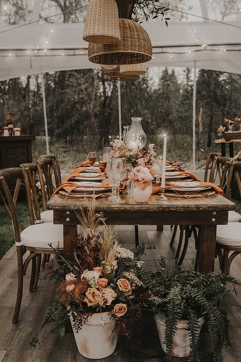 Intimate wooden table decorated with natural elements such as terracotta pots, rust coloured napkins, woven basket decor, ferns, pottery and ceramics