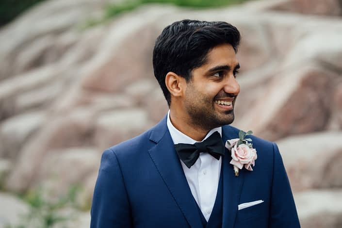 Groom, Jason, wearing a navy suit and blush boutonniere made with spray roses and eucalyptus.