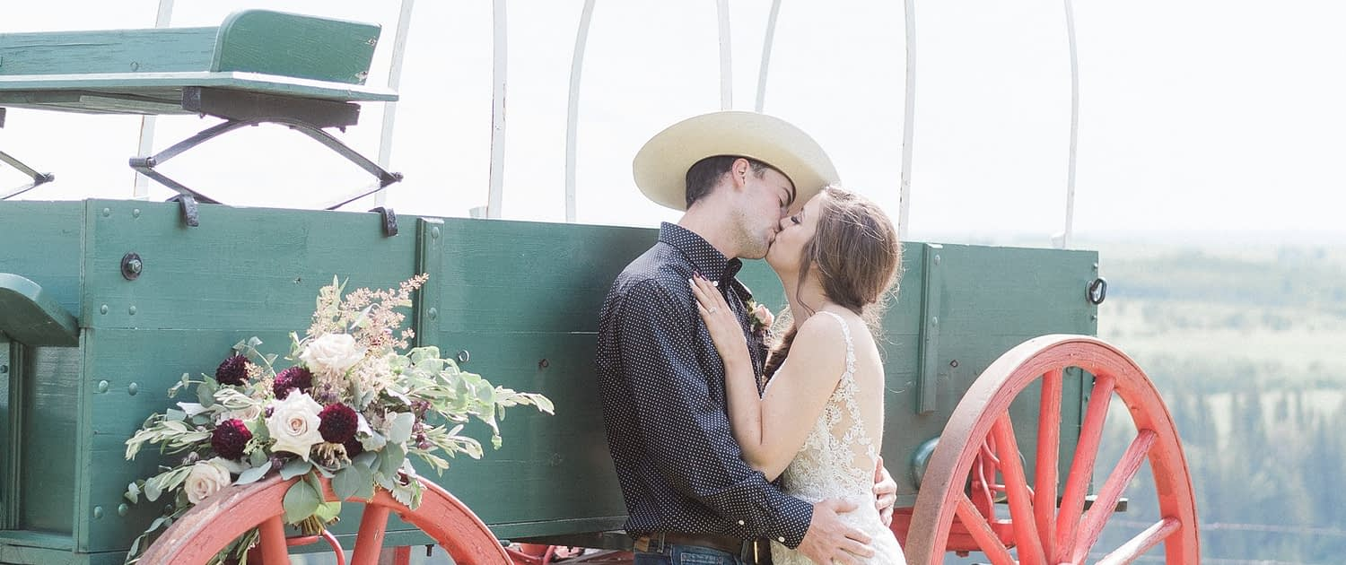 Bride and cowboy groom kissing next to a chuckwagon with a burgundy country chic bridal bouquet on the wheel.