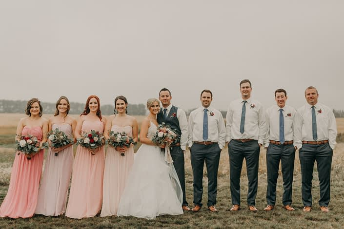 bridal party with bridesmaids in blush dresses of various shades and holding bouquets with white and red and blush roses and eucalyptus groomsmen in grey pants with blue ties and boutonnieres with red spray roses
