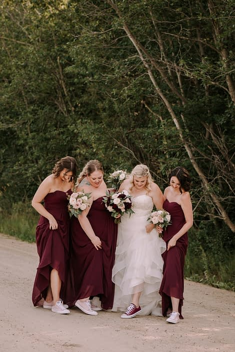 Tamara and Kyle's Rustic Chic Burgundy and Blush bride and bridesmaids with blush and burgundy bouquets and converse shoes.