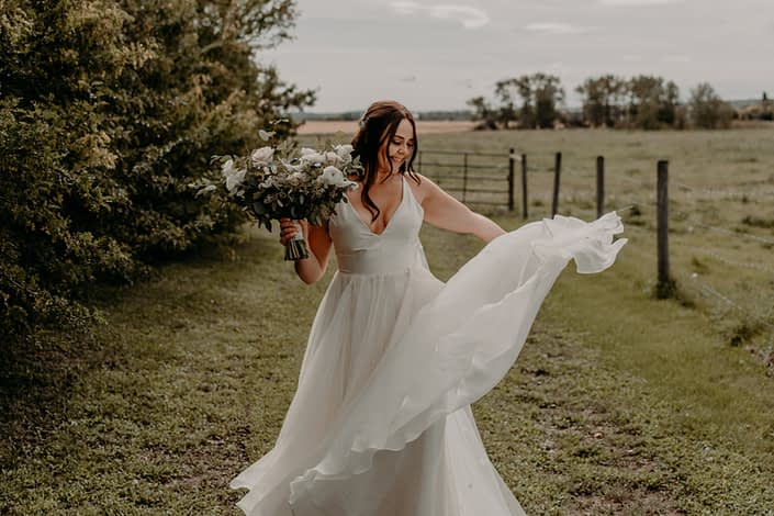 Bride Erika twirling her white bridal gown and carrying a blush, ivory and white bridal bouquet with fresh eucalyptus greenery.