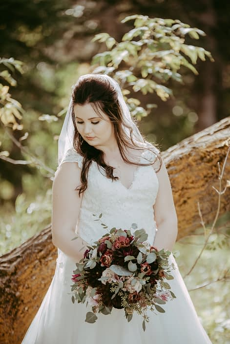 Bride with rustic burgundy and dusty rose bridal bouquet designed with quicksand roses, lisianthus, ranunculus and dahlias