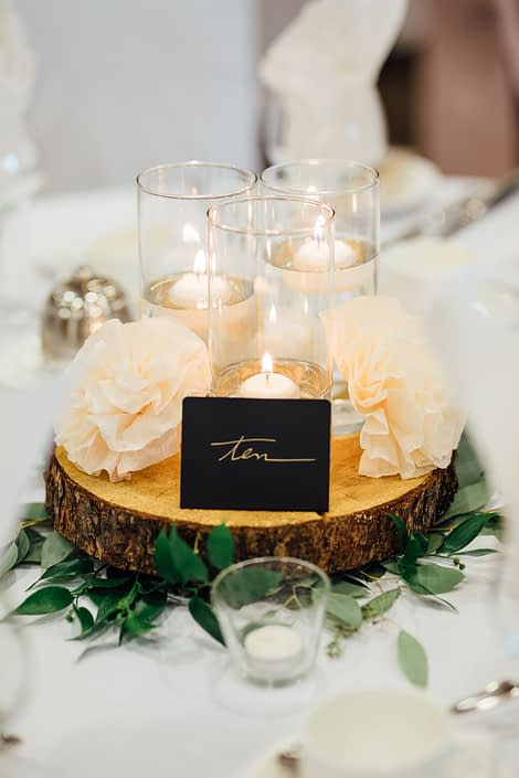Centrepieces for Jill and Jason's romantic blush Calgary Zoo Wedding designed with fresh loose greenery such as eucalyptus and italian ruscus at the base of a wood cookie with pillars of floating candles and paper flowers.