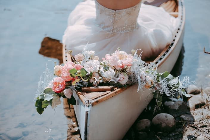 Canoe and a bridal bouquet featuring coral charm peonies, blush roses, silver plumosa and eucalyptus greenery.