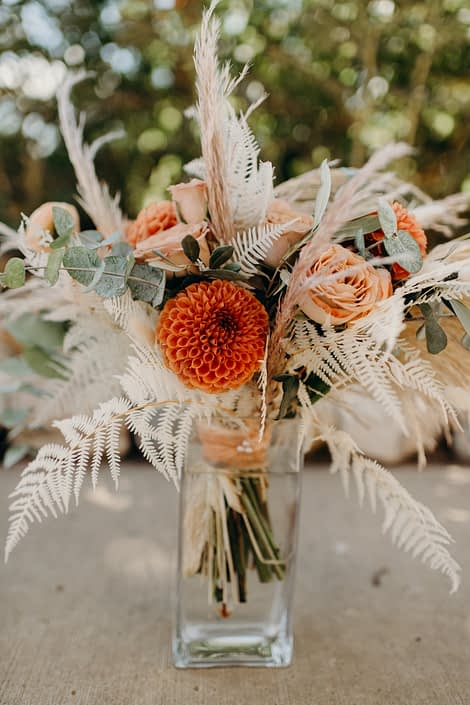 Orange Boho Bridal Bouquet designed with bleached bracken fern, bunny tail, dahlias, ranunculus, cappuccino roses, eucalyptus, olive branches and pampas grass