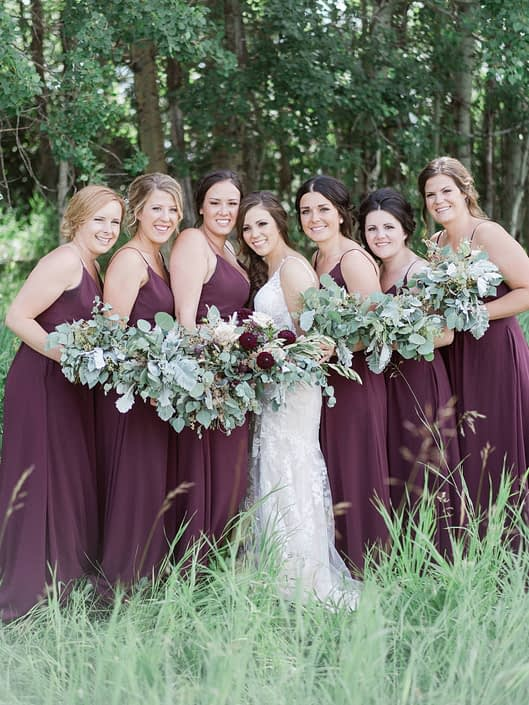 Bride and bridesmaids wearing burgundy and carrying greenery bouquets; bridal bouquet has a burgundy country chic feel and featured dahlias, quicksand roses, olive branches, dusty miller and seeded eucalyptus.