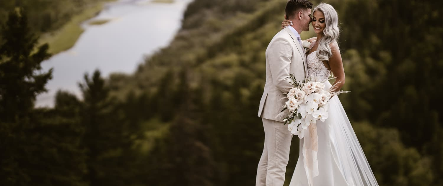 Boho glam bride and groom with cascading bridal bouquet designed with quicksand roses, phalenopsis orchids, pampas grass, olive branches and silver dollar eucalyptus.