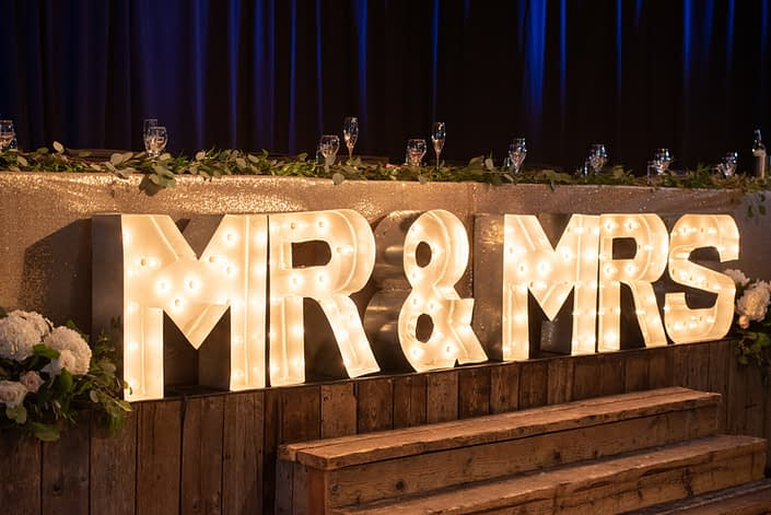 Fresh loose eucalyptus and Italian ruscus greenery atop the head table with a lit up Mr & Mrs sign.