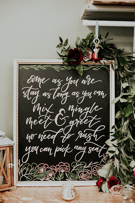 Rustic Boho Chic Wedding - come as you are stay as long as you can sign draped with garland made of greenery, and red and blush roses