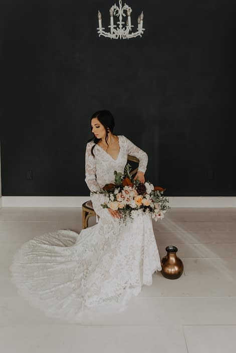 Neutrals Styled Shoot with Down the Aisle - Bride wearing lace gown holding neutral bouquet of orchids, roses, magnolia leaves and eucalyptus greenery.