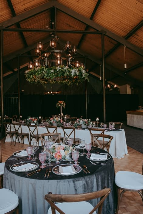 Reception hall at Canyon Ski Resort for the Open House 2019; greenery garland on chandelier; round table with grey table cloth, blush goblets and vineyard chairs; rectangle tables with ivory tablecloths, blush goblets, silver lucca flatware, rustic vineyard chairs; floral arrangement designed with coral charm peonies, blush roses and eucalyptus greenery.