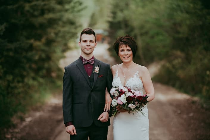 Bride and Son; Bride holding a pink and burgundy bridal bouquet featuring Sarah Bernhardt peonies, blush and white ranunculus, black baccara roses, blackberry scoop scabiosa, burgundy tulips and accented with pale pink astrantia and seeded eucalyptus greenery; son wearing a boutonniere made with blush spray roses and burgundy ninebark leaves and juniper.