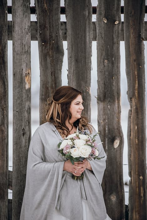 Bride wearing grey shawl and holding a mauve and ivory bouquet designed with astilbe, eryngium, white o'hara garden roses, ranunculus, amnesia roses, playa blanca roses and eucalyptus