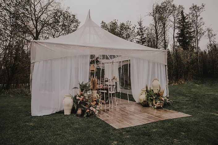 Small white tent decorated with pottery and boho decor with ferns, pampas grass and rust coloured flowers