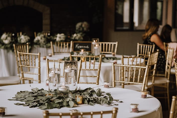 centerpiece at canyon ski resort with white linens, gold chivari chairs and centerpiece of eucalyptus greenery and cylinder vases with candles
