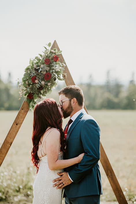 Bride and groom kissing at wedding ceremony in front of wooden triangle archway arrangement made of black bacarra roses and burgundy ranunculus