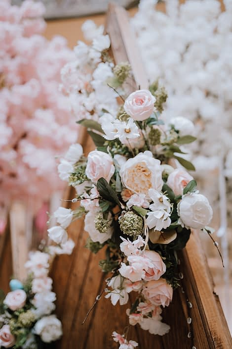 White, peach, pink and green artificial botanicals at the top of the wooden mountains backdrop
