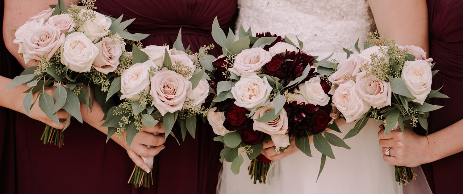Tamara and Kyle's Rustic Chic Burgundy and Blush Wedding bouquets; bridal bouquet featuring burgundy dahlias, white o'hara garden roses, black baccara roses, quicksand roses, and eucalyptus; bridesmaid bouquet designed with blush roses and greenery.