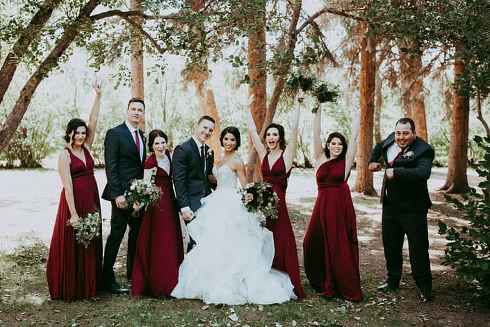 Rikki Lee and Jake's burgundy and dark grey bridal party cheering with boutonnieres and bouquets