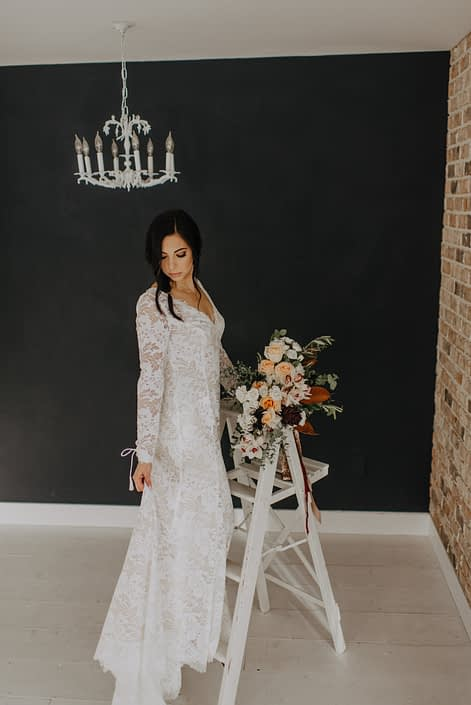 Neutrals Styled Shoot with Down the Aisle - Bride wearing lace gown standing on a ladder holding a neutral coloured bouquet with orchids, peach roses, magnolia leaves and eucalyptus, tied with trailing ribbons.