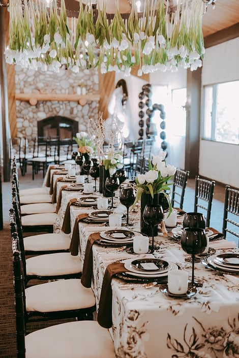 Rectangular table decorated with an ivory and black marie noir linen tablecloth, black and white plates, black goblets and black chiavari chairs; black vases villed with toffee and quicksand roses, white tulips and mazanita branches; tulips hanging from the chandelier.