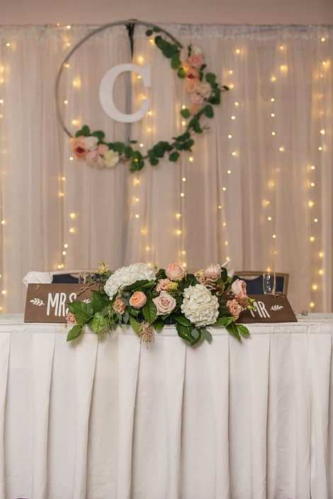 Megan and Steven's Rustic Pastel Wedding head table decor and floral arrangement made of white hydrangeas, Juliet garden roses, quicksand roses, salal, and eucalyptus greenery.